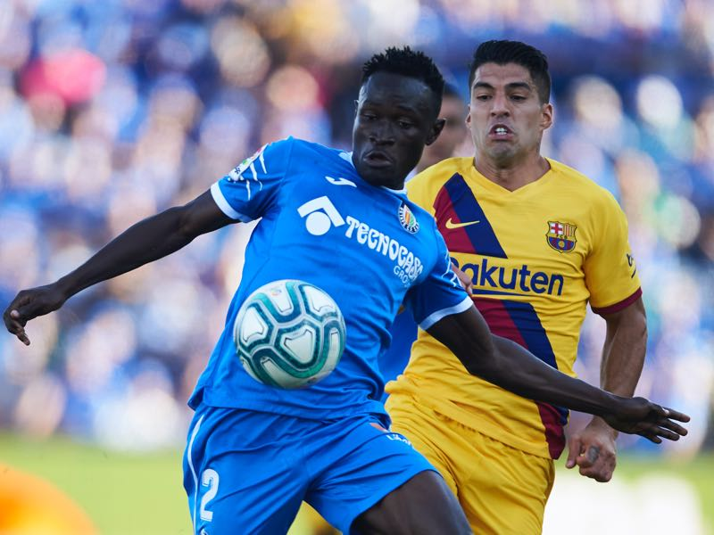 Luis Suarez of FC Barcelona duels for the ball with Djene Dakonam of Getafe CF during the Liga match between Getafe CF and FC Barcelona at Coliseum Alfonso Perez on September 28, 2019 in Getafe, Spain. (Photo by Aitor Alcalde/Getty Images)
